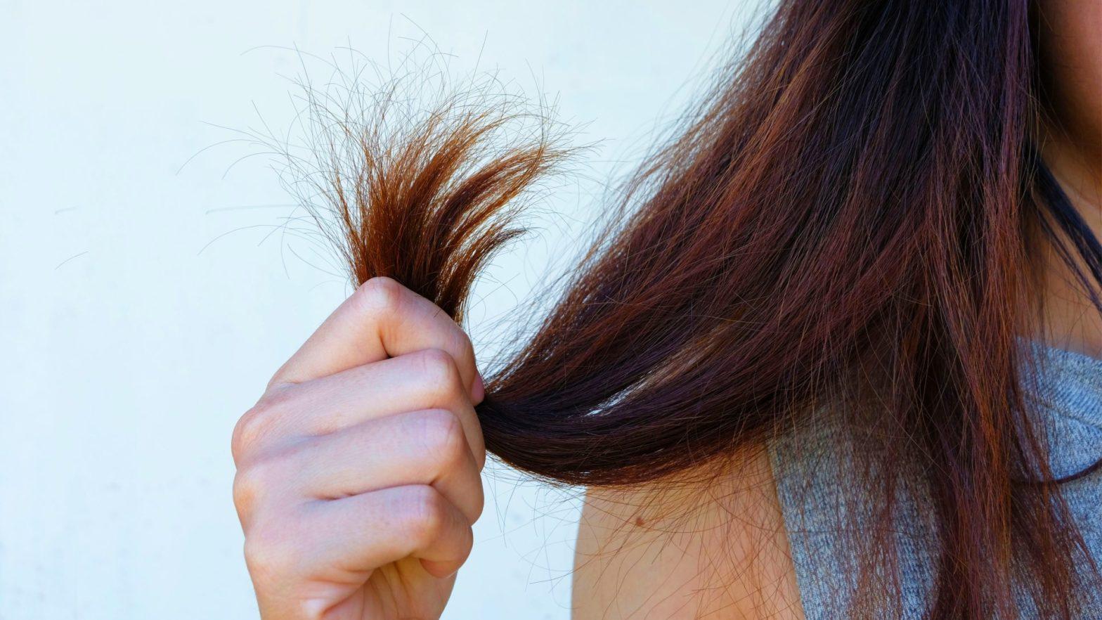 Mulher segurando as pontas do cabelo ressecado